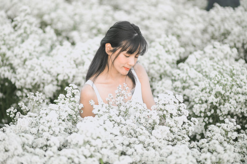 Full length of young woman on white flowering plants