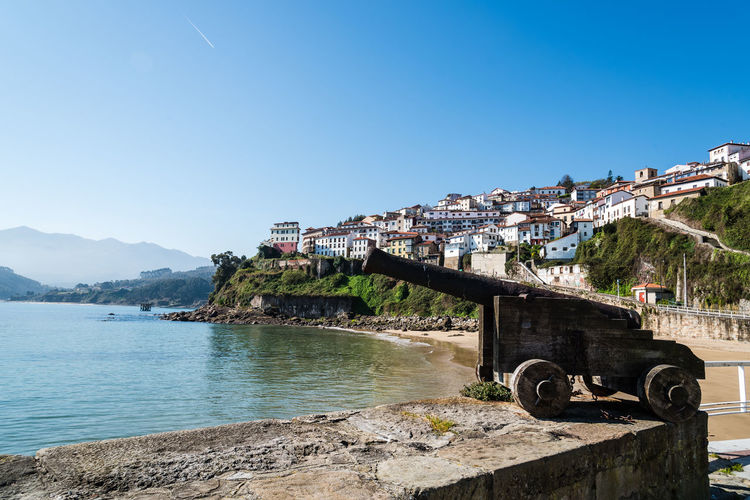 View of the harbour and the town of Lastres. Old gun on foreground Lastres Asturias SPAIN Europe Gun Bay Cityscape Harbor Harbour Sjy Water Dock Sky Built Structure Architecture Nature Clear Sky Building Exterior Mountain Copy Space Day Sea No People Scenics - Nature Outdoors