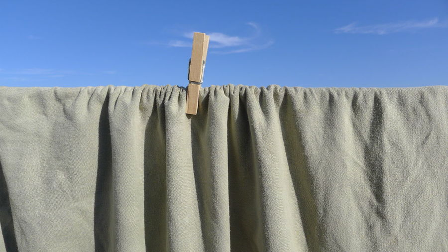 Close-up of fabric on clothesline against sky