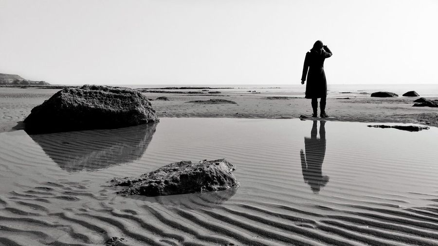 Rear view of person standing on beach against clear sky