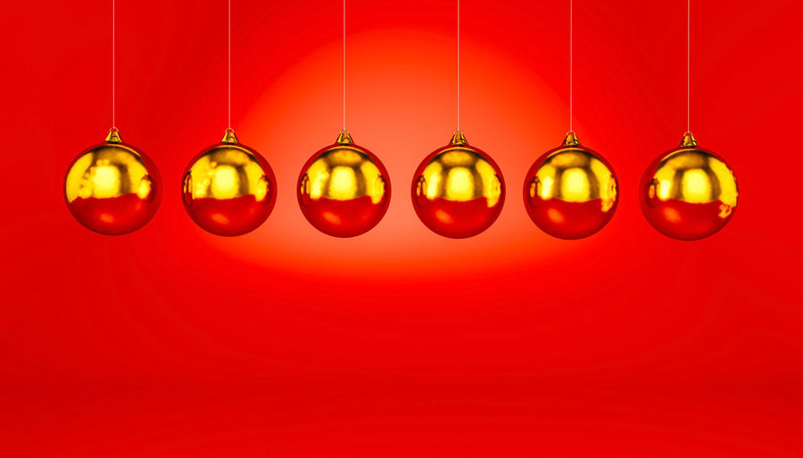 Multi colored lanterns hanging against red wall