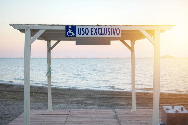 Information sign on beach against clear sky
