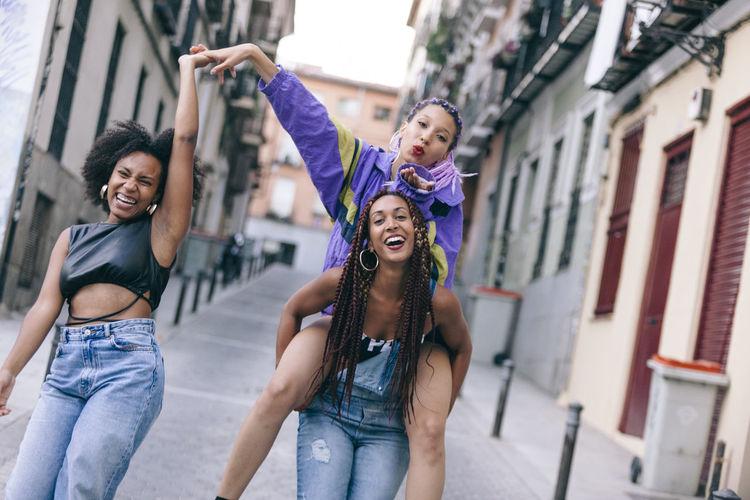Happy female friends walking in city