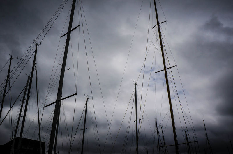 Low angle view of silhouette sailboat in sea against sky