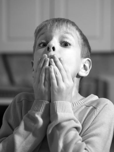 Close-up portrait of shocked boy covering mouth at home