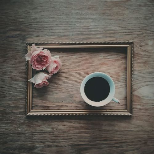 Directly Above Shot Of Coffee Cup And Flowers In Frame On Table