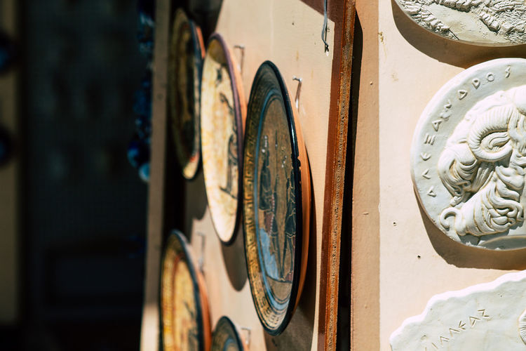 Close-up of old plates hanging on wall