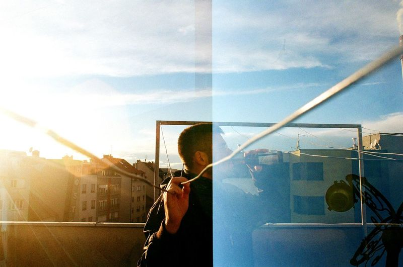 Man skateboarding on glass window against sky