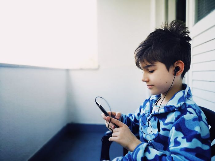 Boy looking away while using smart phone