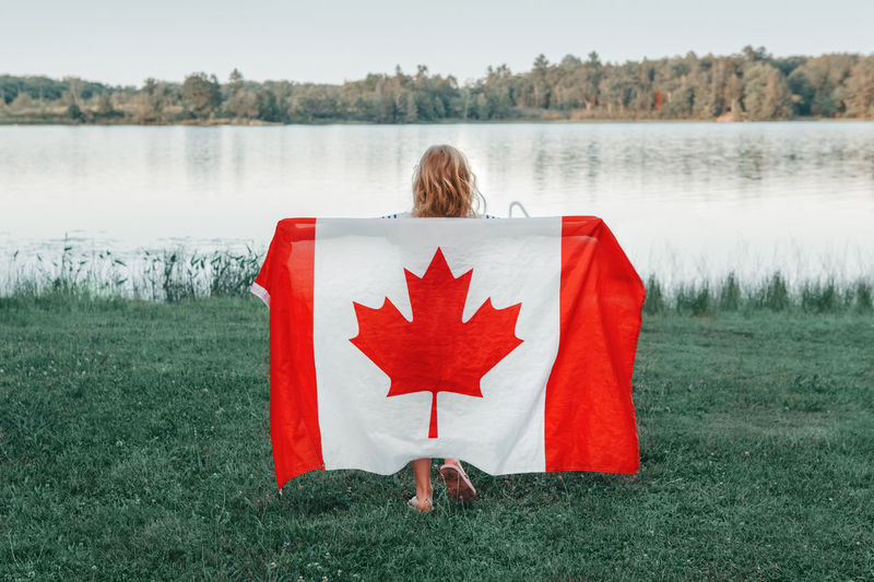 Girl wrapped in large canadian flag by muskoka lake in nature. canada day celebration outdoor.