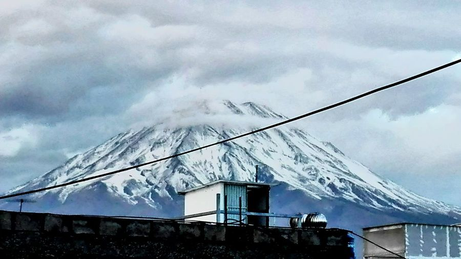 Low angle view of snow covered mountain against cloudy sky