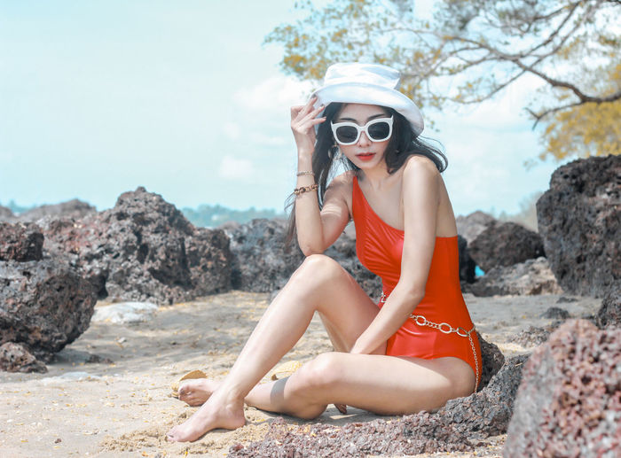 Young woman wearing sunglasses sitting on rock at beach