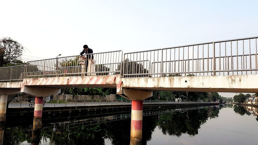 Man standing on footbridge over river against clear sky