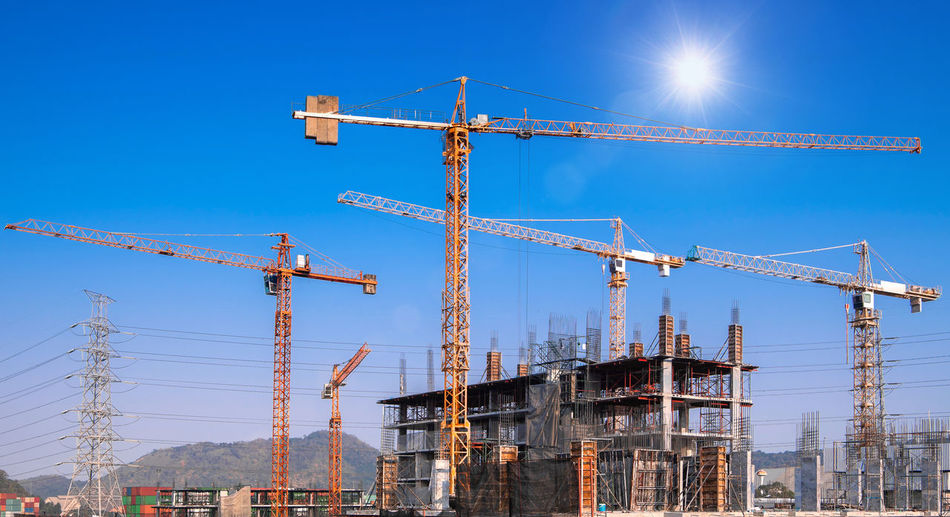 Low angle view of cranes against blue sky