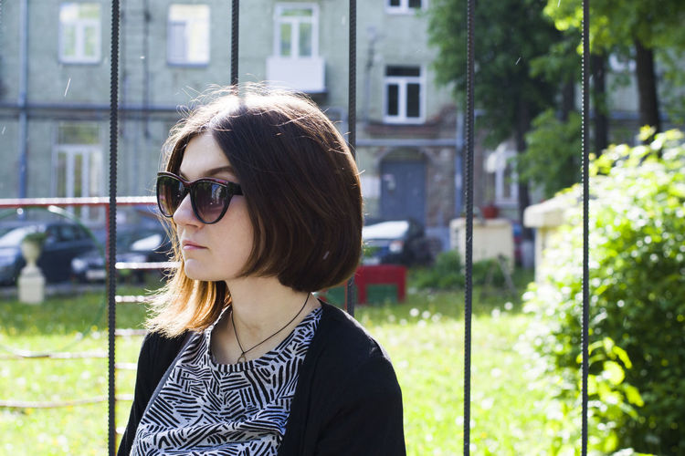 Young Woman Wearing Sunglasses While Standing By Fence