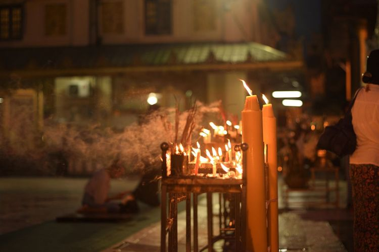 Illuminated candles and incense outside temple at night