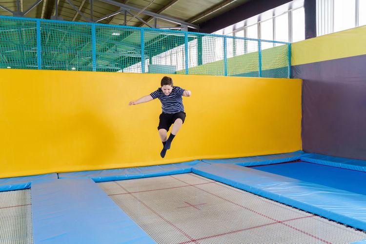 Full length of man jumping against wall