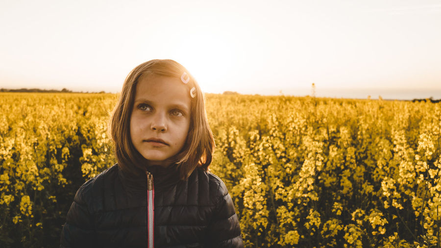 Close-Up Of Thoughtful Girl Standing At Farm During Sunset