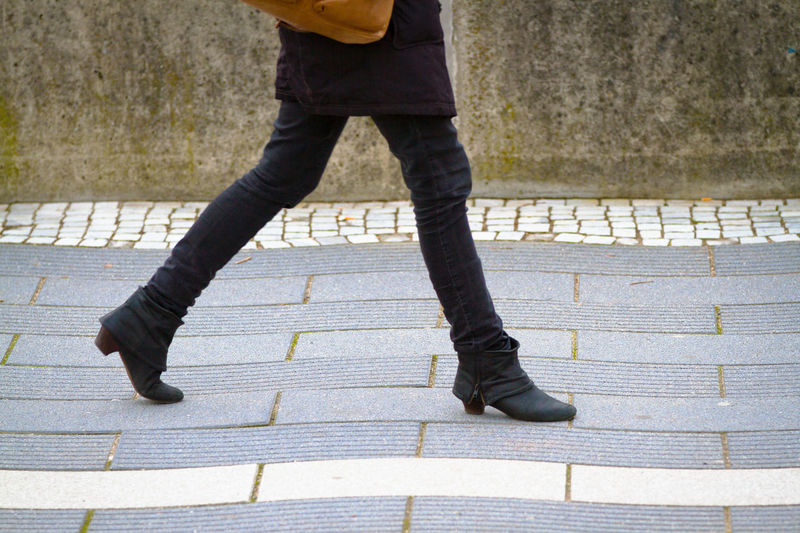 Low section of man walking on footpath