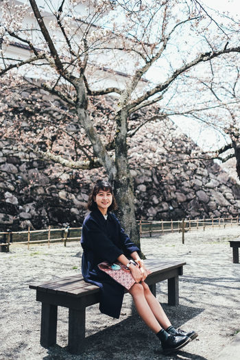 Sakura One Person Tree Sitting Plant Young Adult Leisure Activity Real People Lifestyles Full Length Casual Clothing Bench Front View Nature Day Flowering Plant Young Women Flower Looking At Camera Portrait Outdoors Cherry Tree Springtime Cherry Blossom Sakura Sakura Blossom