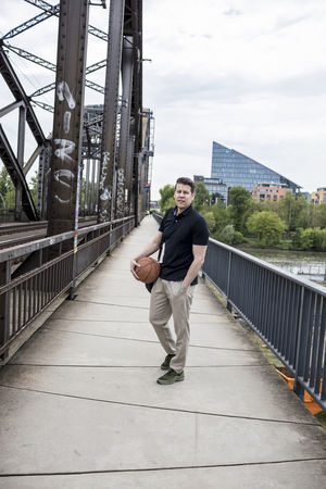 Casual dressed man with a sports bag on his shoulder and a basketball in one hand poses for the camera with an urban setting in the background. Long shot. Basketball Cloudy Day Khaki Pants Life Style Long Shot Looking At Camera Man Standing Bridge Casual Clothing Caucasian Day Golf Shirt Hand In Pocket Long Shot Male Model Posing River Shoulder Strap Sport Sports Bag Summer Urban White