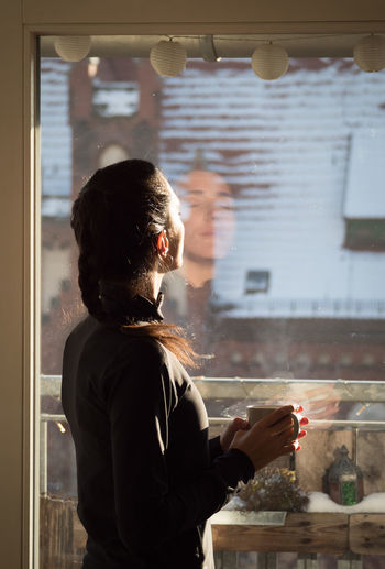 Side view of man looking through window