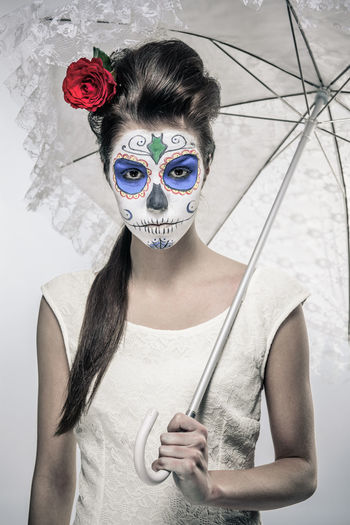 Portrait of young woman holding mask