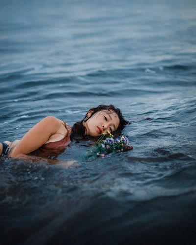 Portrait of woman lying in sea