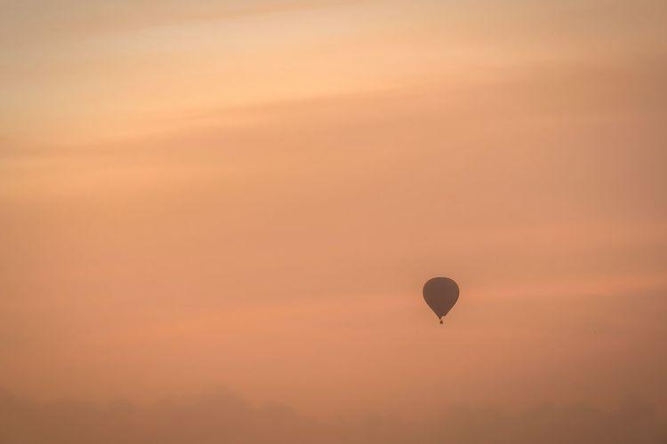 Silhouette hot air balloon against orange sky