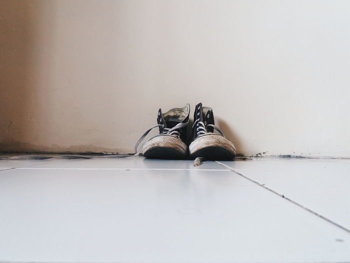 Shoes On Floor Against Wall At Home
