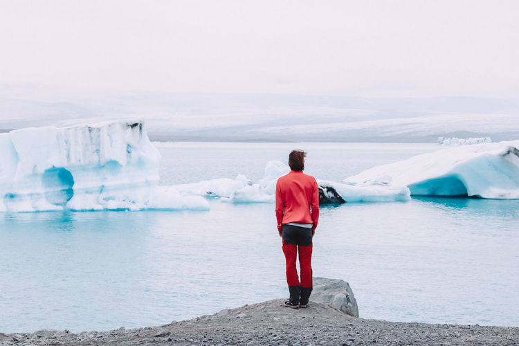 Rear view of man standing by the glaciers