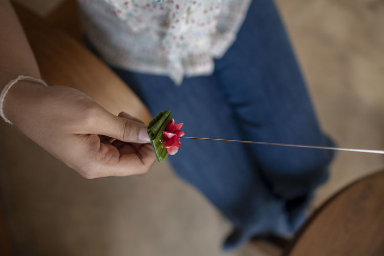 Close-Up Of Woman Holding Flower In Needle