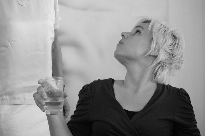 Woman Holding Drinking Glass And Looking Up