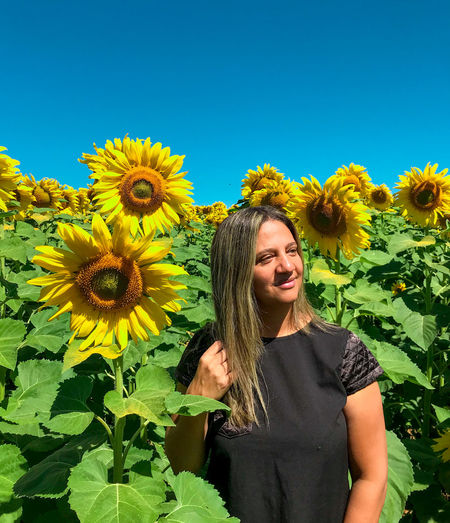 Portrait of smiling woman with sunflower against plants