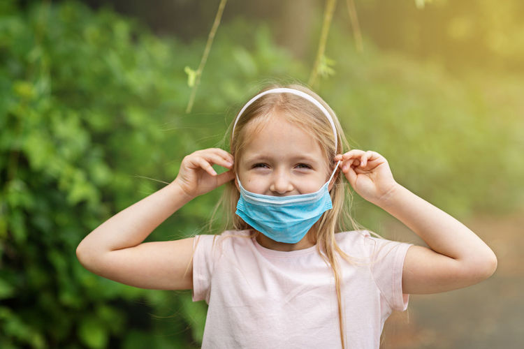 Happy little girl takes off protective medical mask from face outdoors. victory over coronavirus