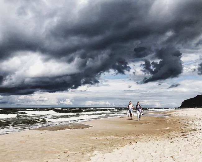 People standing on beach against cloudy sky