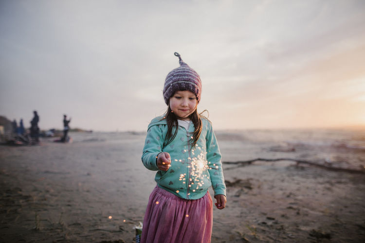 Girl standing on beach against sky during sunset