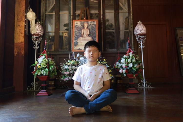 Portrait of boy sitting on floor