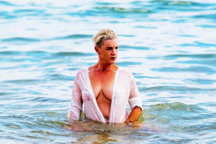 Seductive mature woman standing in sea