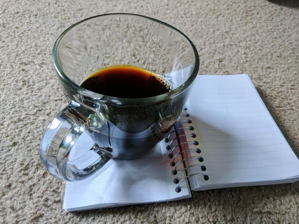 EyeEm Selects Coffee Notebook Writing Creativity Carpet Floor Drinking Glass Food And Drink Drink Refreshment Black Coffee Glass Half Full Indoors  Freshness Close-up Day No People Relaxation