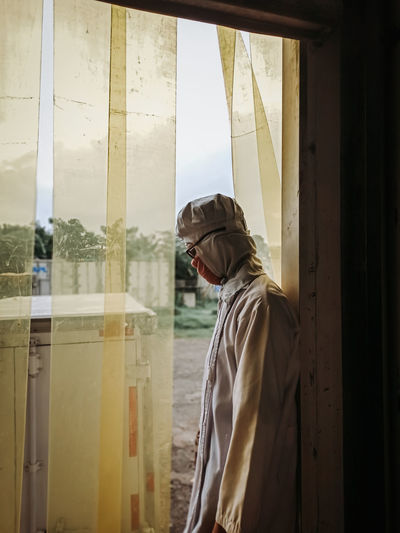 Side view of man looking at window