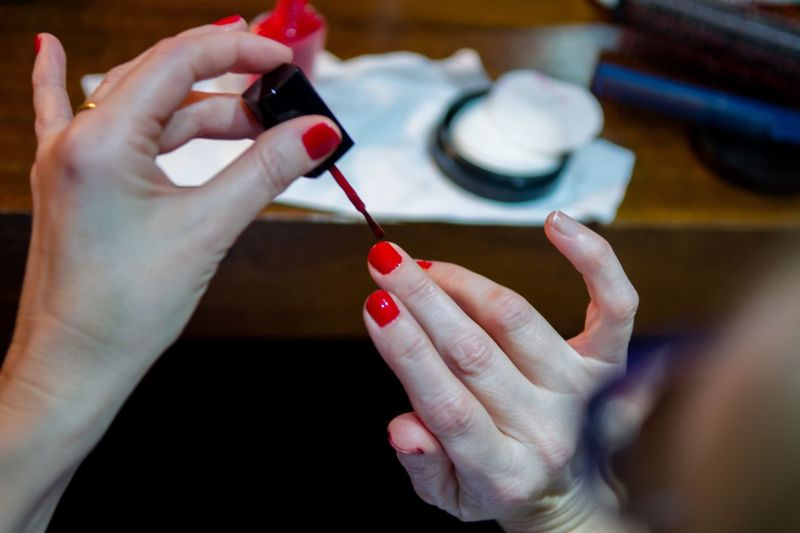 Cropped hands of woman applying red nail polish