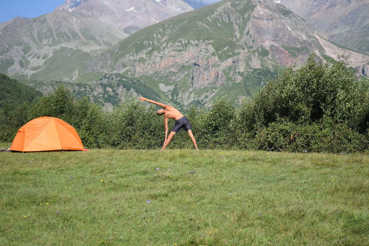 Rear view of man doing yoga in field against mountain