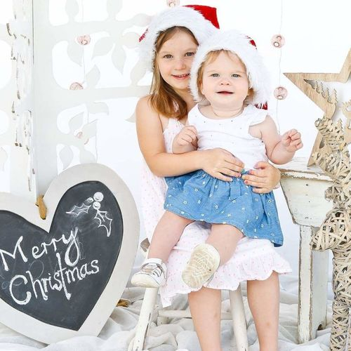 Portrait of girl with sister by heart shape merry christmas text on stool