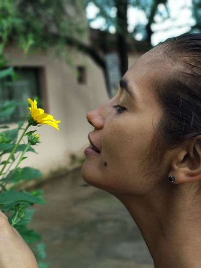 Profile View Of Woman Smelling Yellow Flower Blooming On Plant