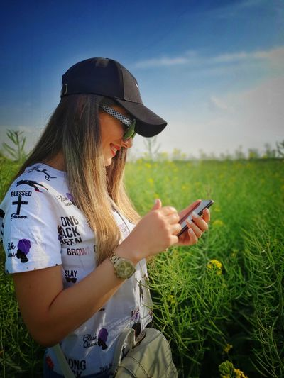 Young woman using mobile phone on field against sky