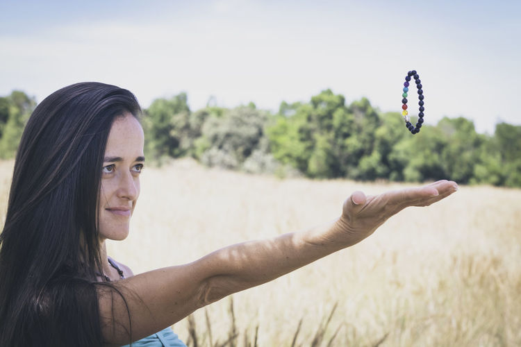 Portrait of smiling young woman against sky while levitating bracelet.