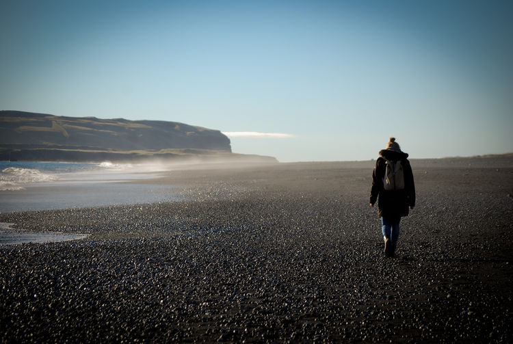 Rear view of woman walking on shore against clear sky