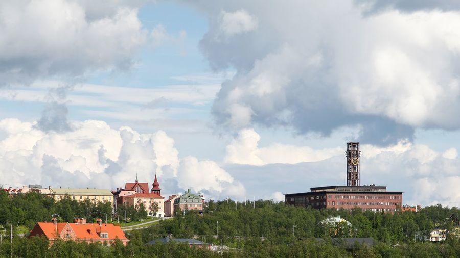 Panoramic view of buildings in town against sky
