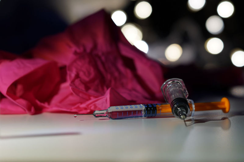 Close-up of syringes and pink fabric